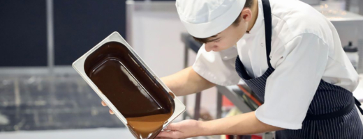 Photo of Ben pouring chocolate into a mould in patisserie and confectionery competition