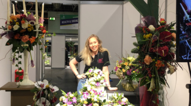 Photo of Clara, Squad UK Floristry competitor standing next to a floral display
