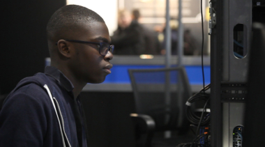 Photo of Isaac, IT Network Systems Administrator competitor looking at computer screen