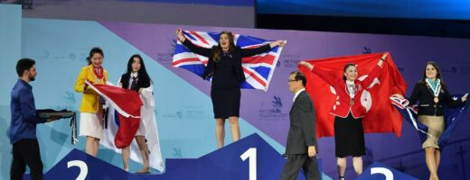 Photo of competitors carrying UK flags on stage at WorldSkills Abu Dhabi 2017