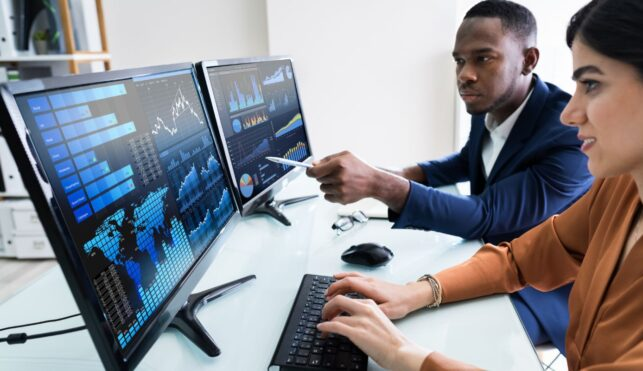 Photo of accounts looking at charts on computer screens
