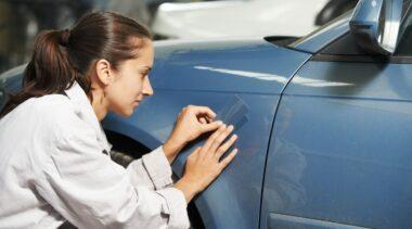 Photo of auto body repair technician looking at car body