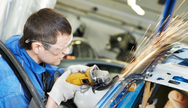 Photo of automotive body repair using machine on outside of car frame