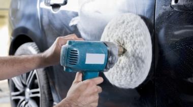 Photo of automotive body repair using buffer machine on car surface