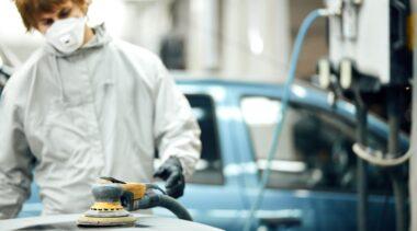 Photo of automotive refinishing using buffer machine on car surface