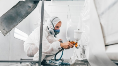 Photo of automotive refinishing using a spray gun to paint car