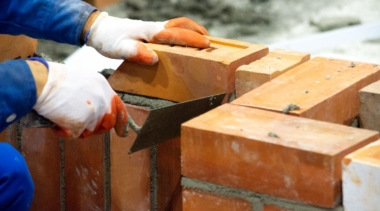 Photo of a bricklayer placing a brick onto a wall
