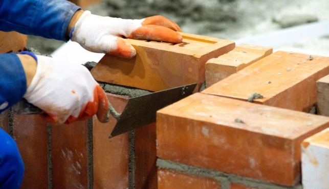 Photo of a bricklayer placing a brick onto a wall