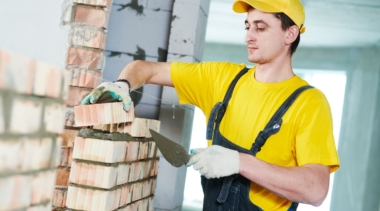Photo of a young bricklayer placing a brick on to a wall