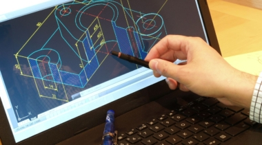 Photo of a CAD Technician pointing at a drawing on a computer screen