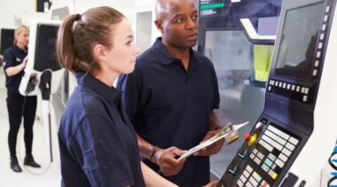 Photo of CNC Machinist looking at CNC machine
