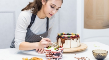 Photo of a confectionery chef placing decoration on top of dessert cups