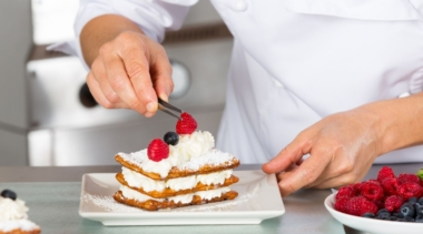 Photo of a confectionery chef placing a raspberry on a mille feuille