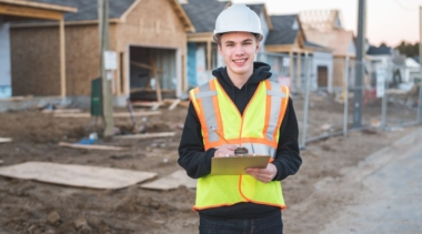Photo of construction project manager on site with a clipboard