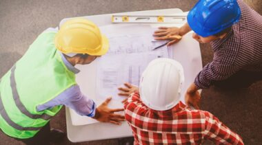 Photo of construction project managers examining drawings