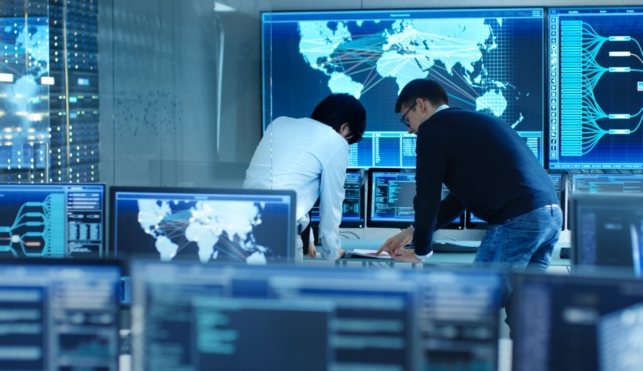 Photo of two cyber intelligence officers in a control room with lots of computer screens