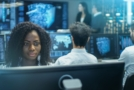 Photo of a cyber intelligence officer in a control room with lots of computer screens