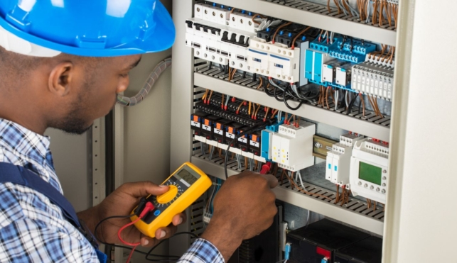 Photo of an electrician examining the inside of a fuse box