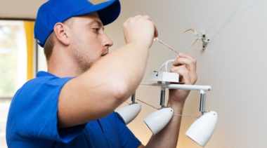 Photo of an electrician fixing a light fitting with a screwdriver