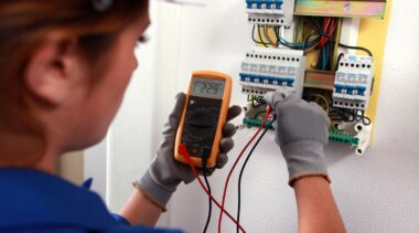 Photo of electronics technician and fuse box