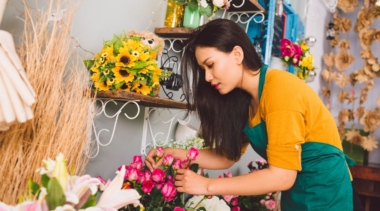 Photo of florist arranging a bunch of pink flowers