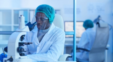 Photo of forensic scientist looking into microscope