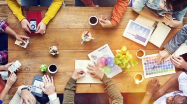 Photo of graphic designers gathered around a table discussing designs