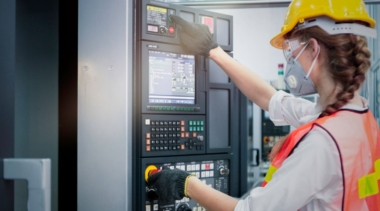 Photo of industrial control technician examining machine display