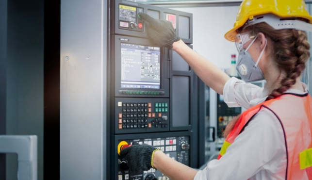 Photo of industrial control technician examining machine display