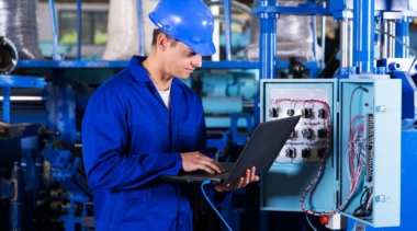 Photo of industrial control technician looking at laptop attached to machinery