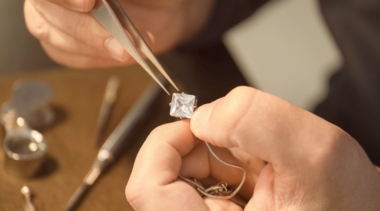Photo of jeweller holding a diamond close up with tweezers