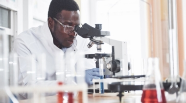 Photo of young lab technician looking into microscope