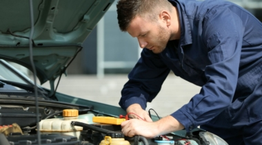 Photo of a young male mechanic examining under the hood of a car