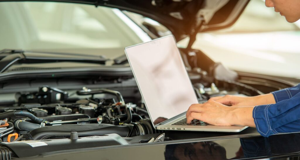 Photo of mechanic using computer to diagnose issues under the hood of the car