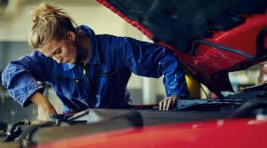 Photo of a young female mechanic examining under the hood of a car