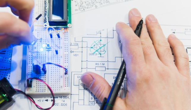 Photo of a mechatronics engineer examining a small component part and a drawing