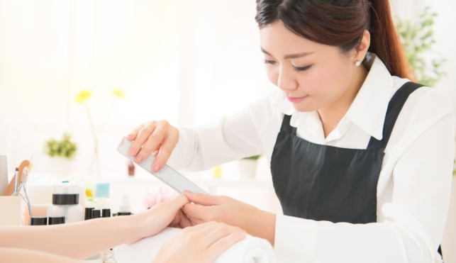 Photo of a young nail technician filing a customer's fingernails in a salon