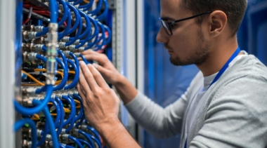 Photo of a young network systems administrator examining a panel of wires