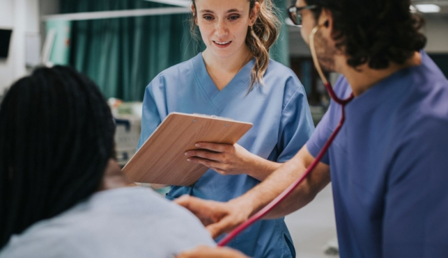Photo of nurse with patient writing on clipboard
