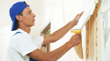Photo of a painter and decorator pulling off wallpaper from a wall