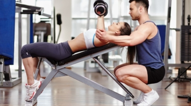 Photo of a personal trainer helping a client to lift weights