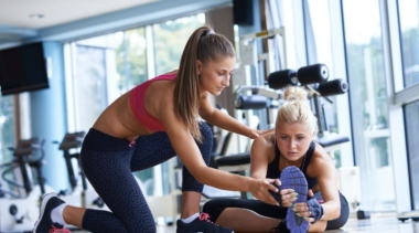 Photo of a young personal trainer helping a client to stretch