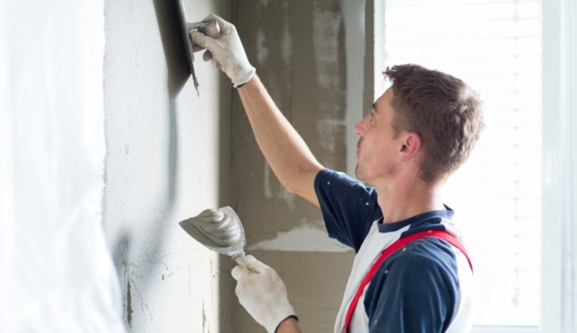 Photo of a young plasterer and drywall worker with a trowel and hawk tool
