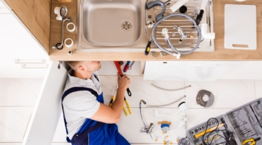 Photo of a young plumber examining the underside of a kitchen sink with some tools
