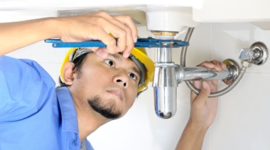 Photo of a young plumber examining the underside of a sink with some tools