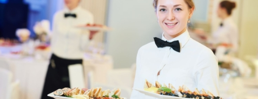 Photo of a young waitress in a restaurant serving platters of food