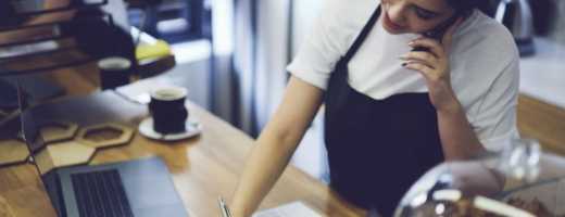 Photo of a young restaurant manager in an apron taking bookings over the phone