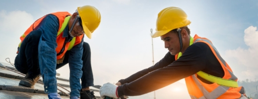 Photo of two roofers in yellow hard hats fixing batons to a roof