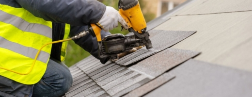 Photo of roofer nailing tiles to a roof