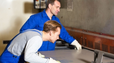 Photo of two sheet metalworkers inspecting a piece of sheet metal